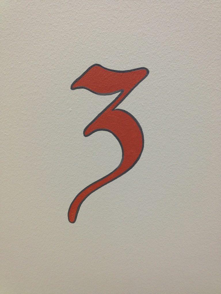 Handmålad siffra som markerar våningsplanet.