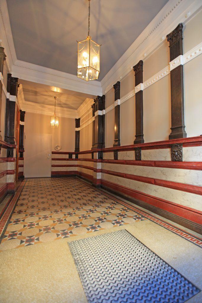 Färgsättning av trapphus med marmorerade väggar och färgsatt takspegel.