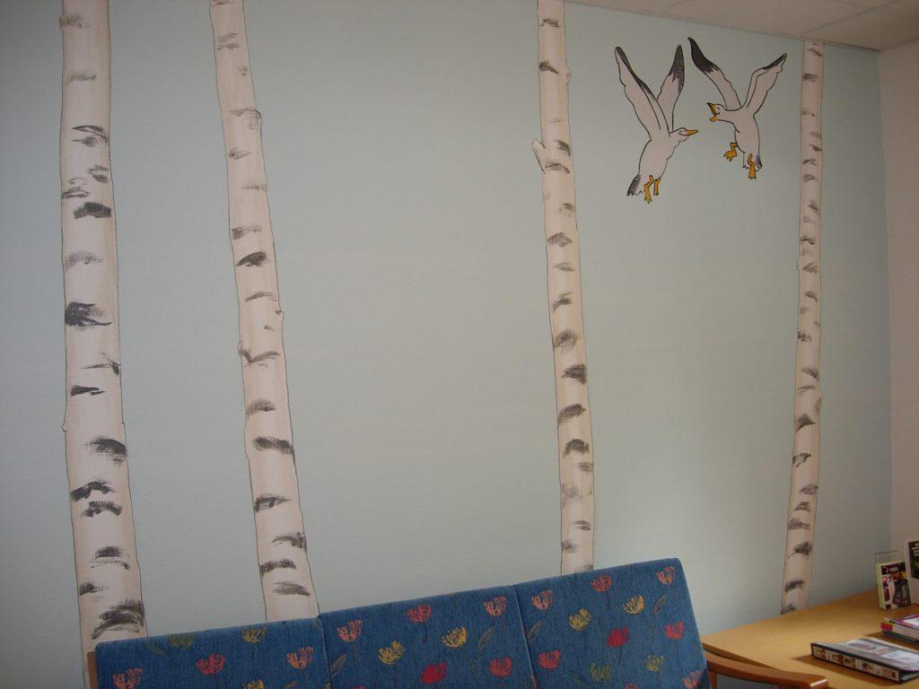 Björkar och skrattande måsar på väggmålning i väntrummet.